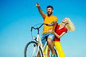 Young Hippie Couple On Sky Blue Background. Beautiful Smiling Girl And Bearded Hipster Man Is Riding poster