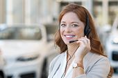 Beautiful customer support wearing headset and looking at camera. Portrait of smiling woman customer poster