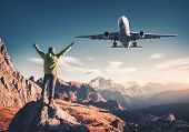 Airplane And Man On The Stone With Raised Up Arms Against Mountains At Sunset. Happy Sporty Man, Fly poster