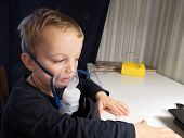 The Little Boy Is Breathing With The Help Of Compressor Nebulizer, Electronic Nebulizer With Medicat poster