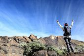 Hiker cheering. Happy hiking woman with arms raised overcoming challenges. From hike on volcano Teid