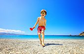 Shot Of An Adorable Little Boy Having Fun At The Beach On Vacation. Kid Wearing Sunglasses And Smili poster