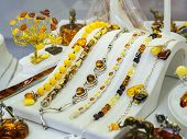 Baltic Amber Jewelry Bracelets On A White Stand On The Showcase Of A Jewelry Store. Amber In Silver  poster