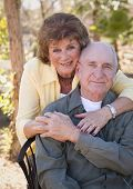 foto of oxygen  - Senior Woman Outside with Seated Man Wearing Oxygen Tubes - JPG