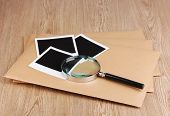 Envelopes with photo papers and magnifying glass on wooden background