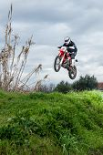 Enduro Bike Rider In Action. Jump On Mud And Grass Terrain. poster