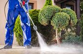 Caucasian Worker In His 30s With Pressure Washer Cleaning Residential Driveway. Garden And Home Surr poster