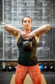 Young Female Athlete Holding A Kettlebell Weight poster