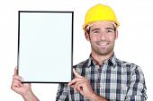 stock photo of peppy  - Construction worker holding up a blank bulletin board - JPG