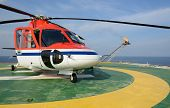 picture of helicopter  - The helicopter park on oil rig to pick up worker with gas flare and blue sky backgroung - JPG