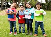 stock photo of kindergarten  - Happy group of school kids holding notebooks outdoors - JPG