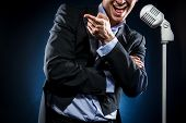 pic of singing  - Man in elegant black suit with vintage microphone singing - JPG