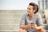 Happy Female Athlete Listening To Music While Resting