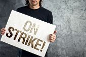 image of striking  - Man holding banner with ON STRIKE printed protest message - JPG