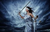 Постер, плакат: Femida Goddess of Justice with scales and sword wearing blindfold against dramatic stormy sky