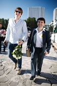 stock photo of mans-best-friend  - Groom and his friend - two smiling men walking down a street one carrying flowers and the other in a suit wearing a buttonhole flower