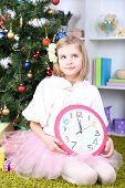 Little girl holding clock near Christmas tree in room