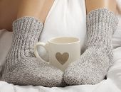 image of hot-chocolate  - A cup of coffee or hot chocolate and female feet with socks on a white sheets - JPG