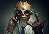 picture of gas mask  - Man wearing gas mask and headphones making rock sign - JPG