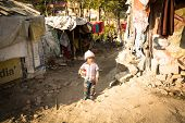 KATHMANDU, NEPAL - DEC 16, 2013: Unidentified poor children near their houses at slums in Tripureshw