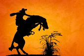 stock photo of buck  - Silhouette of cowboy reigning bucking bronco spooked by something in the nearby sagebrush - JPG