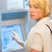 image of automatic teller machine  - Lady buying a railway ticket at the automatic ticket vending machine with touch screen - JPG