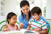 stock photo of homework  - Mother Helping Children With Homework - JPG