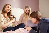 Three Teenage Girls Relaxing In Bedroom Together