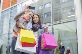 pic of two women taking cell phone  - Female friends with shopping bags taking self portrait through mobile phone against store - JPG