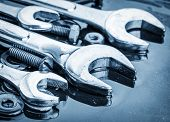 stock photo of reflection  - Set of tools wrenches and bolts toned in metallic blue with reflections - JPG