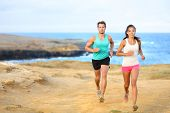 stock photo of country girl  - Sports couple jogging for fitness running in beautiful landscape nature outdoors - JPG