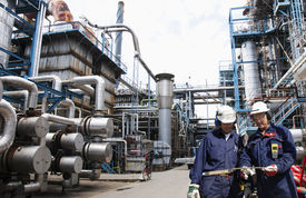 image of refinery  - two oil and gas workers inside large refinery - JPG