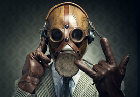 pic of gases  - Man wearing gas mask and headphones making rock sign - JPG