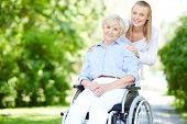 stock photo of wheelchair  - Female caregiver and senior patient in a wheelchair looking at camera outside - JPG