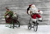 image of snow-slide  - Funny christmas greeting card with Santa on a bike pulling a slide in the snow - JPG