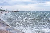 stock photo of gushing  - Gushing surf of a wave smashing against seaport at Thessaloniki Greece - JPG