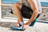 image of ankle shoes  - Fit man gripping his injured ankle on a sunny day - JPG