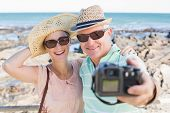 stock photo of take off clothes  - Happy casual couple taking a selfie by the coast on a sunny day - JPG