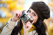 pic of seasonal  - Fashionable happy woman taking photos with retro film camera in autumn season - JPG