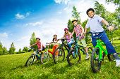 Постер, плакат: Row of children in colorful helmets holding bikes