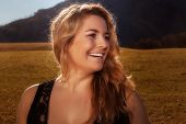 stock photo of bosoms  - Portrait of a laughing blond girl with long golden hair in the autumn sun  - JPG