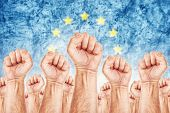 picture of union  - Europe Labor movement workers union strike concept with male fists raised in the air fighting for their rights European Union flag in out of focus background - JPG