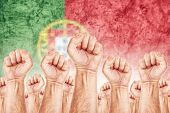 picture of labourer  - Portugal Labour movement workers union strike concept with male fists raised in the air fighting for their rights Portuguese national flag in out of focus background - JPG