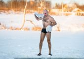 foto of freezing  - man wipes towel after swimming in the freezing - JPG