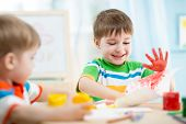 pic of kindergarten  - smiling kids playing and painting at home or kindergarten or playschool - JPG
