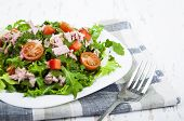 stock photo of masago  - Mixed salad with tuna and tomatoes on a wooden background - JPG