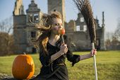 stock photo of pale skin  - Witch with pale skin appleknife and pumpkin - JPG