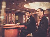foto of roulette table  - Two fashionable men in suits behind table in a casino - JPG