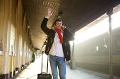 pic of waving hands  - Portrait of a young man waving hand and calling by mobile phone at train station - JPG