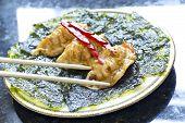foto of pot roast  - Fried Japanese dumplings on crispy roasted seaweed and red pepper garnish - JPG
